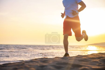 Low section view of man running on beach at sunset