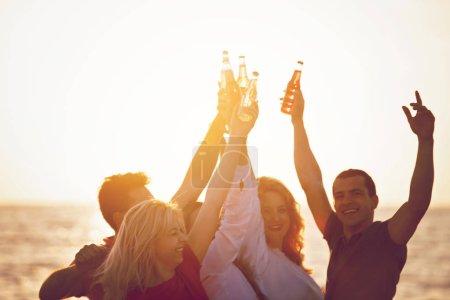 Photo pour Groupe de jeunes heureux avec des boissons à la plage sur le beau coucher de soleil d'été - image libre de droit
