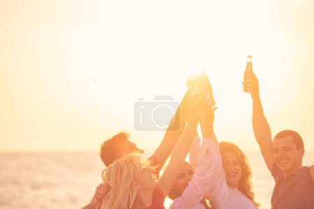 Photo for Group of happy young people with drinks at the beach on beautiful summer sunset - Royalty Free Image