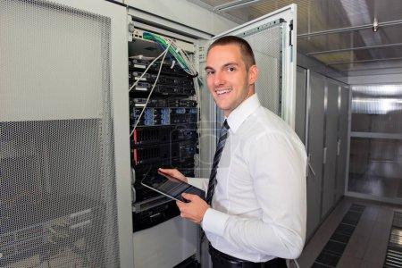 Photo pour Entreprise beau jeune homme ingénieur dans la salle de serveur de datacenter - image libre de droit
