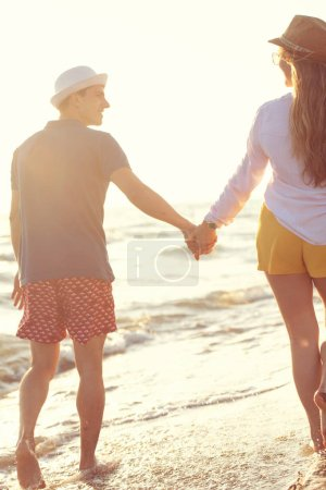 Foto de Despreocupado hombre y mujer caminando en la orilla del mar, vista hacia atrás - Imagen libre de derechos