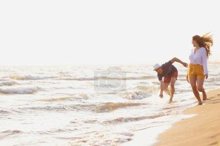 man and woman walking at sea shore at sunset