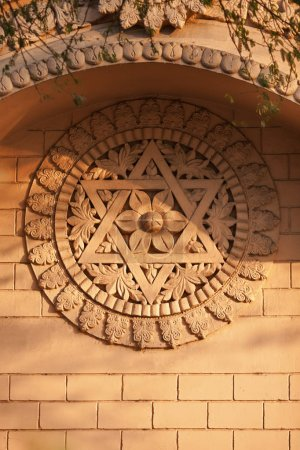 Old bas-relief on a temple wall - a Hindu six-pointed star, and blooming flower in a centre of composition, in beams of the evening sun.