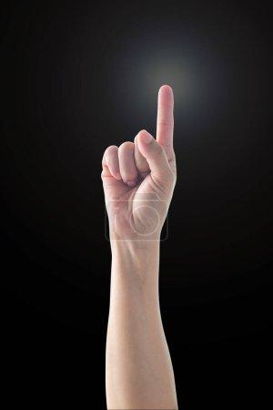 Photo pour Pointant la main de la femme doigt avec la lumière de la jante isolé sur fond noir (chemin de coupe) pour le numéro un 1, montrant la direction, aller droit devant, bons ides - image libre de droit
