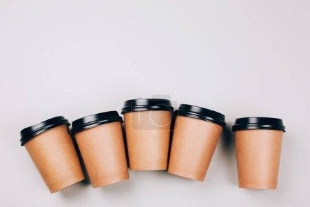 Photo pour Plusieurs tasses de craft brun de café pour aller sur fond rouge et gris. Orgelet plat Lapointe. - image libre de droit