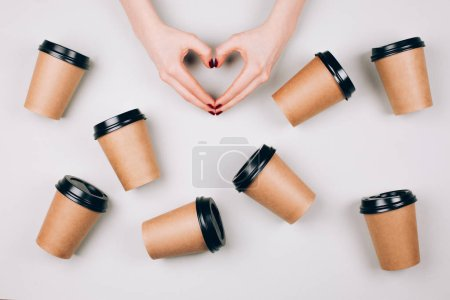 Photo pour J'adore le concept du café. Deux mains faisant coeur entre de nombreuses tasses en papier de café à emporter - image libre de droit