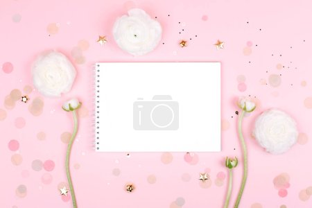 notebook with blank page with beautiful spring ranunculus flowers on pink pastel background with sparkles