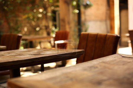Wooden table in focus and blurred background of cozy cafe