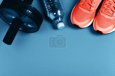 Photo for Living Coral sneakers on blue background. Fitness background. Color of the year 2019. Main trend concept. - Royalty Free Image