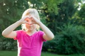 Young Girl Looking Through Heart Hands