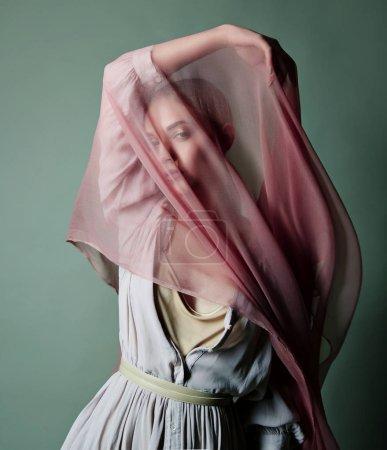 Photo pour Une belle jeune fille tendre dans une robe en mousseline de soie est recouvert d'une draperie en tissu mince qui se développe dans le vent. - image libre de droit