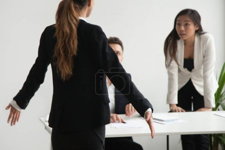 Photo for Female worker is at loss shrugging shoulders, being blamed by colleagues presenting her arguments, accusing her of company business failure. Concept of quarrel in work team, controversy, disagreement - Royalty Free Image