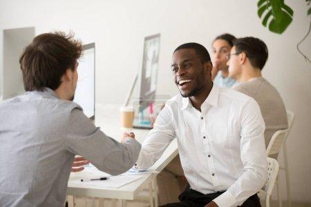 aufgeregter freundlicher afrikanischer Manager schüttelt Kunden oder Kollegen die Hand