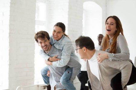 Foto de Empresarios jóvenes alegres riendo y teniendo divertido paseo en tándem, empleados felices disfrutando jugar juego juntos en la rotura, equipo amable sonriente profesionales oficina actividades concepto creativo - Imagen libre de derechos