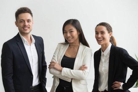Photo pour Millénaire employés de bureau professionnelle multiethnique souriante regardant la caméra, asiatique et caucasien groupe créatif des gens d'affaires heureux trois costumes ensemble, portrait d'une équipe diversifiée avec succès - image libre de droit