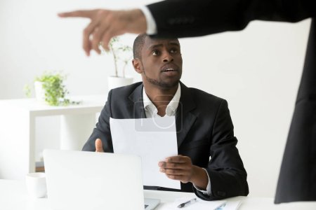 Photo for Frustrated shocked African American worker being fired, holding dismissal notice, while Caucasian employer pointing at door asking to leave. Concept of racial discrimination, employment termination - Royalty Free Image