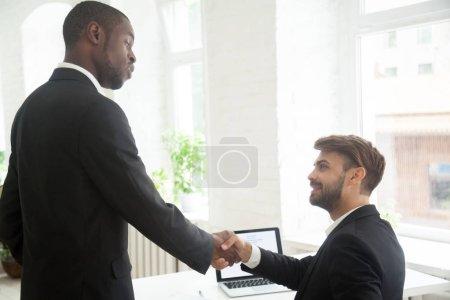 Photo pour Handshaking sérieux patron afro-américain pour féliciter fier caucasienne subordonné avec fermeture affaire rentable, stratégie commerciale réussie, bon travail personnel, réalisations, se félicitant de nouveau membre - image libre de droit