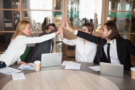 Excited work team giving high five celebrating shared achievemen