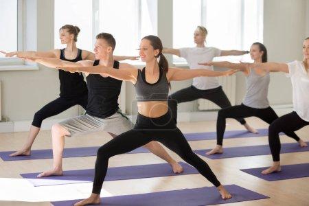 Photo pour Groupe de jeunes gens sportifs pratiquant des cours d'yoga, faire exercice guerrier deux, Virabhadrasana 2 pose,, yogi étudiants travaillant à l'intérieur dans le club de sport, studio. Vie consciente, notion de perte de poids - image libre de droit