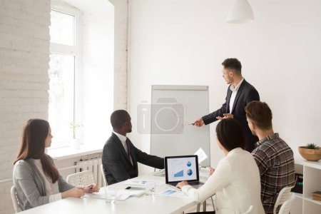 Photo for Confident Caucasian speaker making presentation on flipchart in front of diverse colleagues during board meeting, talking about shares and sales, coach mentoring employees. Concept of leadership - Royalty Free Image
