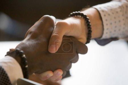 Les gens multiraciaux poignée de main saluant avec succès ou sucer