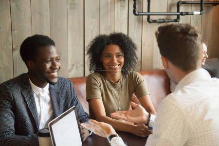 Photo pour Planificateur de mariage caucasien consultant couple noir sur les idées de mariage dans un café, courtier ou agent immobilier parler à des clients afro-américains, compte tenu des offres immobilières dans une atmosphère décontractée dans un café - image libre de droit