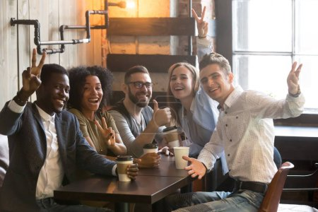 Smiling diverse millennial colleagues posing for picture in cafe