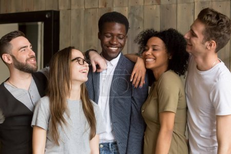 Photo for Happy multiracial millennial friends posing for picture at friendly meeting in coffeeshop, smiling diverse students standing laughing at funny joke, having fun together in cafe. Ethnicity concept - Royalty Free Image