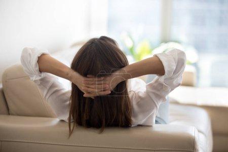 Photo pour Vue arrière de la détente féminine au canapé confortable en cuir à la maison, tenant la main sur la tête, femme reposant sur le canapé, se rafraîchissant pendant la journée dans un appartement lumineux moderne, penché et rêvant d'avenir. Vue arrière - image libre de droit