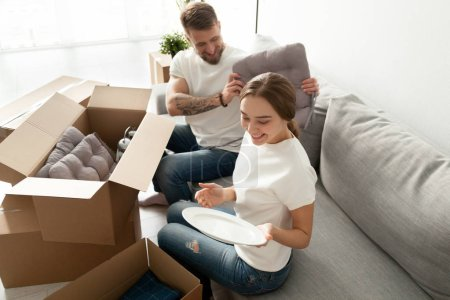 Photo for Happy young couple having fun unpacking boxes sitting on sofa, moving to new rented house, millennial owners settling in first shared home opening cartons after relocating. Living together concept - Royalty Free Image