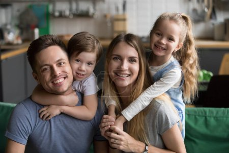 Photo for Head shot portrait of happy parents piggybacking son and daughter sitting on sofa together, smiling family with cute kids bonding embracing at home, children hugging mother father looking at camera - Royalty Free Image