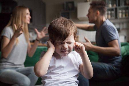 Photo pour Fils de gamin frustré met les doigts dans les oreilles, ne pas écouter le bruyants parents faisant valoir, a souligné garçon d'âge préscolaire souffrant de maman et papa combats criant, famille des conflits en pâtissent concept enfant - image libre de droit