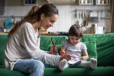 Photo pour Baby-sitter souriante et préscolaire kid fille dessin avec des crayons, assis sur le canapé ensemble, une seule mère et fille enfant jouant ayant des activités familiales amusantes et créatives à la maison concept - image libre de droit