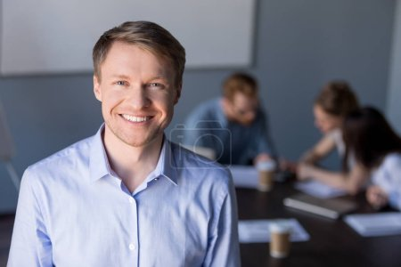 Photo for Portrait of smiling middle-aged male employee posing during company team meeting in boardroom, confident happy businessman looking in camera, making picture for corporate catalogue during briefing - Royalty Free Image