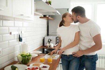 Photo pour Romantique jeune couple embrasser dans la cuisine tout en cuisinant le petit déjeuner ensemble, les amateurs de millénaire profiter matin heureux préparer la nourriture à la maison, homme et femme câlin et se passionner près de la table - image libre de droit