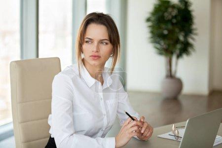 Photo pour Femme d'affaires sérieuse réfléchie pensant à une solution de problème d'entreprise ou la planification d'un nouveau projet de travail dans le bureau, cher écrivain féminin regardant loin à la recherche d'inspiration sentiment de manque d'idées - image libre de droit