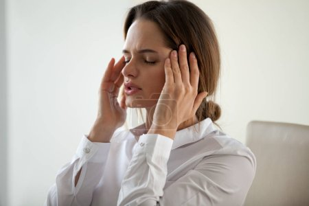 Photo for Young woman feeling strong headache attack concept, exhausted tired businesswoman massaging temples to relieve pain feeling migraine, stressed fatigued lady suffering from pain in aching head - Royalty Free Image