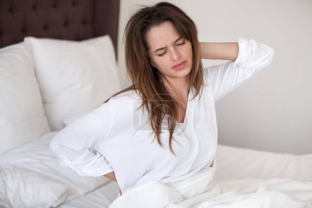 Photo for Unhappy young woman waking up in uncomfortable bed feeling ache in back pain massaging tensed muscles of stiff neck after sleep on bad mattress in incorrect posture, fibromyalgia and backache concept - Royalty Free Image