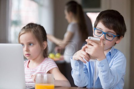 Photo for Boy and girl busy using gadgets in kitchen, siblings watch video or cartoon on laptop and play games on smartphone, small kids addicted to new technology, children having fun with devices - Royalty Free Image