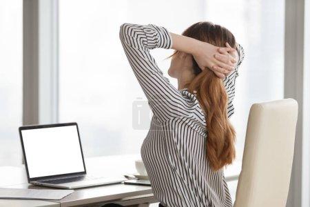 Photo pour Concept de bureau relax. Femme étirant les mains derrière la tête dans une chaise de bureau ergonomique après de longues heures de travail à l'ordinateur portable avec écran maquillé, prendre une pause, faire des exercices simples assis sur le lieu de travail - image libre de droit