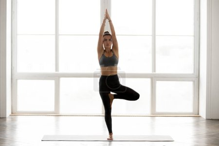 Photo for Young sporty attractive woman practicing yoga, doing Vrksasana exercise, Tree pose, working out, wearing sportswear, grey pants, top, indoor full length, at yoga studio - Royalty Free Image