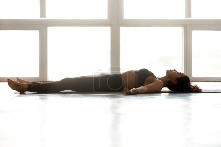 Photo for Young sporty attractive woman practicing yoga, doing Dead Body exercise, Savasana, Corpse pose, working out, wearing sportswear, grey pants, top, indoor full length, at yoga studio, side view - Royalty Free Image