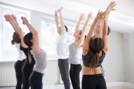 Photo for Group of young sporty people practicing yoga lesson, doing Tadasana exercise, mountain pose, working out, indoor full length, yogi students training in sport studio club. Well-being concept - Royalty Free Image