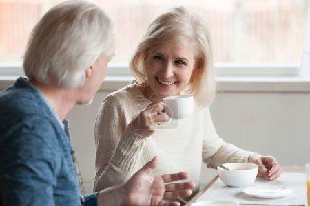 Photo pour Souriant belle femme mûre d'âge moyen boire du thé au café en écoutant un homme plus âgé parler pendant le petit déjeuner, couple de personnes âgées heureux famille manger avoir une conversation agréable à la date à la maison à caf - image libre de droit