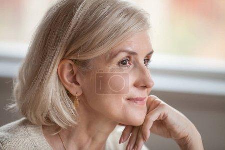 Photo pour Rêveuse réfléchie femme séduisante mature relaxante espérant penser à un avenir heureux, souriante dame d'âge moyen âgée regardant loin réalisant des pensées positives se sentant optimiste dans une bonne attente - image libre de droit