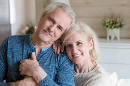 Photo for Happy affectionate mature old man and woman embracing looking at camera, middle aged retired romantic family couple cuddling posing, love care devotion in senior people marriage, headshot portrait - Royalty Free Image