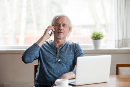 Photo for Senior mature retired man talking on the phone making call sitting with laptop, old middle aged elderly male speaking by mobile at home contacting ordering enjoying conversation by cellphone - Royalty Free Image