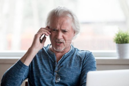 Photo pour Furieux furieux senior homme mature appelant argumentant parler au téléphone contestant se plaindre de problèmes avec ordinateur portable, fou émotionnel mâle criant parler par téléphone mobile appelant le soutien à la clientèle - image libre de droit