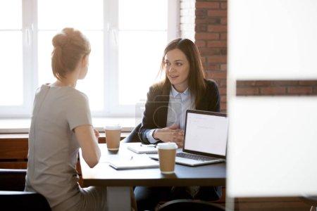 Photo pour Sympathique jeune femmes chefs d'entreprise parler bavarder dans le bureau pendant la pause café, des collègues féminines discuter des plans ou projets lors de réunion avec les ordinateurs portables, les femmes cadres travaillant ensemble de remue-méninges - image libre de droit