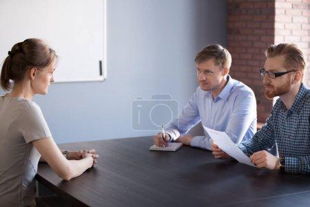 Photo pour Candidat féminin confiant convainquant les gestionnaires sérieux de l'heure masculine dans les compétences professionnelles pour un poste vacant ouvert parler à l'entrevue d'emploi ou négociation d'embauche, concept de première impression, discrimination fondée sur le sexe - image libre de droit